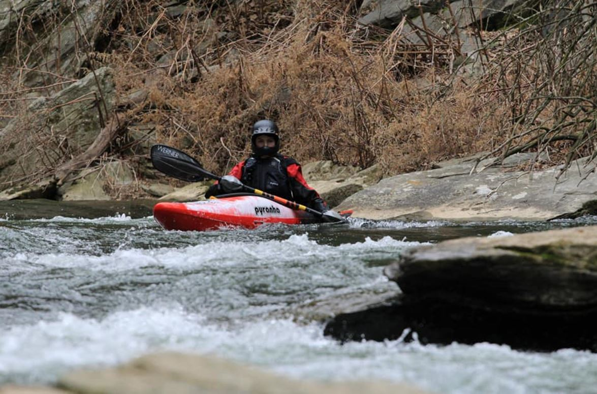 Whitewater kayaker with PFD and helmet
